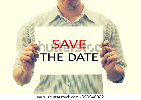 SAVE THE DATE message on the card shown by a man,Gay man hands holding blank advertising card isolated on white background,asian business man show white card in hand,selective focus,vintage color. - stock photo