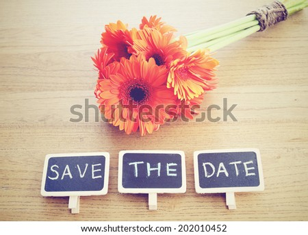 Save the date written on blackboard with flower, nostalgic still life, retro instagram filter effect - stock photo