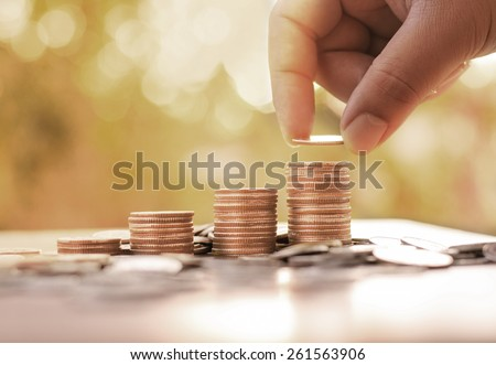 Save,Wealth,Saving money concept,Male hand putting money coin stack growing business with sunlight - stock photo