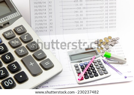 Saving account passbook, Book bank statement with Thai baht Coins, Staples, Calculator, Pen - stock photo
