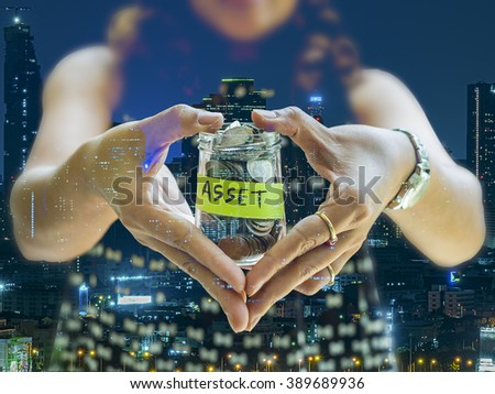 Saving and investment concept image. Double exposure of woman making heart shape holding money jar with ASSET label with night modern cityscape background. Representing saving for invest in asset. - stock photo