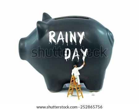 Saving for a rainy day financial concept on a black piggy bank - stock photo