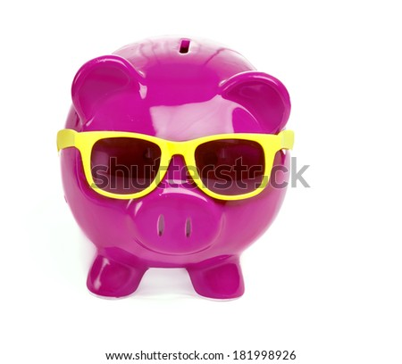 Saving for holiday vacation or retirement.  Piggybank wearing sunglasses - stock photo