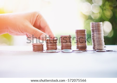 Saving money and Invest concept Hand putting coin money on pile coin stack growing business.Select focus