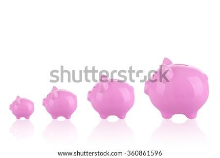 Saving money concept - Growing savings . Different sizes of piggy banks. - stock photo