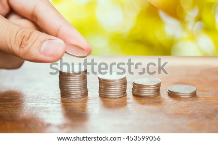 Saving money concept,Male hand putting money coin stack , growing business