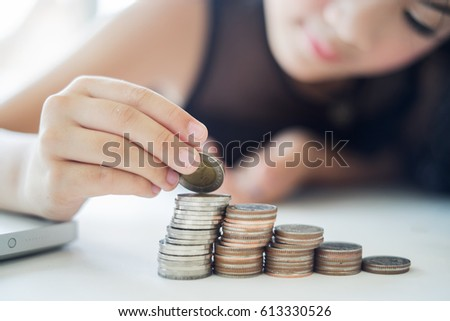 Saving money concept preset by girl hand putting money coins