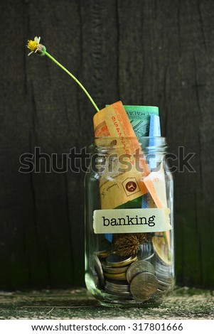 Saving Money Concept With Banking Text Written Label On Glass Jar.Selective Focus And Shallow DOF. - stock photo