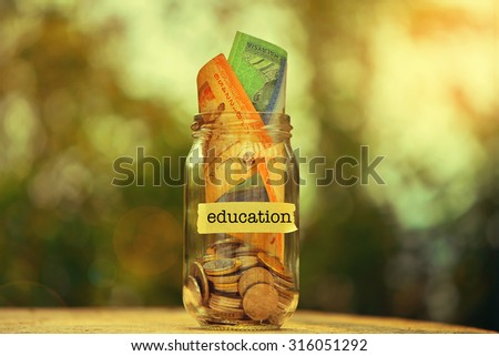 Saving Money Concept With Education Text Written Label On Glass Jar.Selective Focus And Shallow DOF. - stock photo