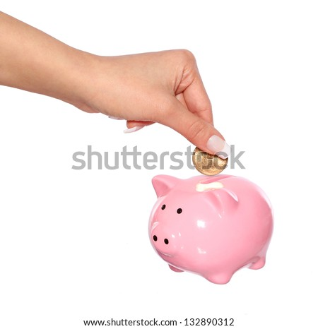 saving money, female  hand is putting coin into piggy bank isolated on white - stock photo