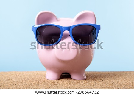 Saving money for retirement, piggy bank on beach with sunglasses. Travel money concept.