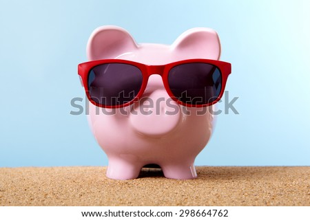 Saving money for retirement, piggybank on beach with sunglasses. Travel money concept.