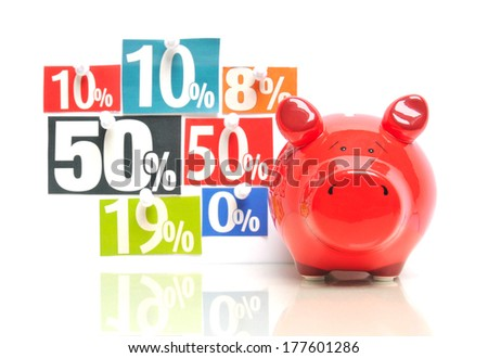 Saving money - red piggy bank with multicolored newspaper percentage adverts - stock photo