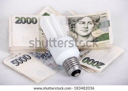 saving money with energy saving bulb concept with czech banknotes crown