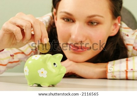 saving money-young woman putting a coin into a green money-box-close up - stock photo