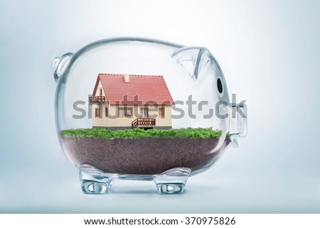 Saving to buy a house or home savings concept with model house inside transparent piggy bank - stock photo