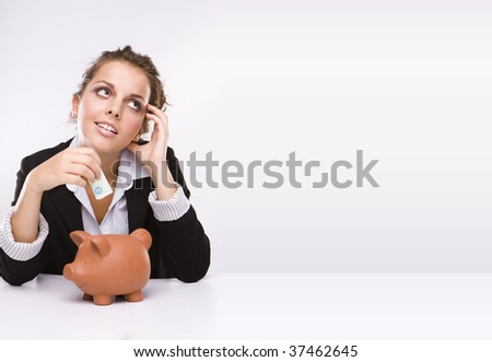 Savings - Business woman at work holding English  pound currency  with a piggy bank dreaming about her shopping - stock photo