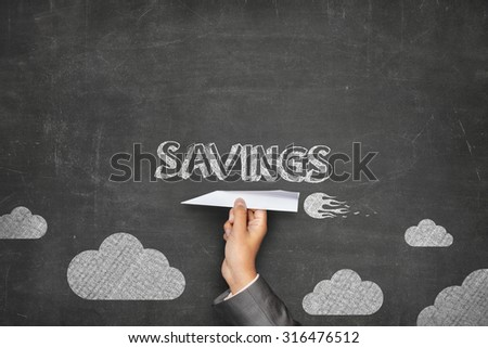 Savings concept on black blackboard with businessman hand holding paper plane - stock photo