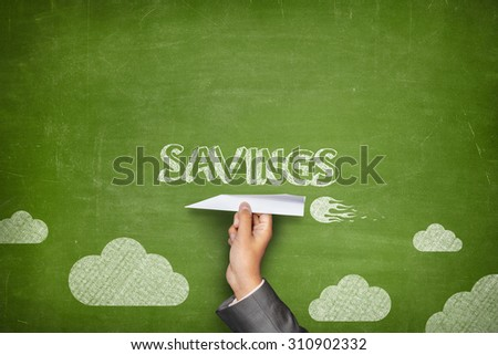 Savings concept on green blackboard with businessman hand holding paper plane - stock photo