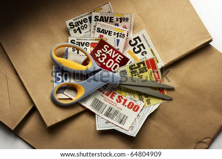 Savings coupons and scissors shot on shopping bags with soft drop shadow - stock photo