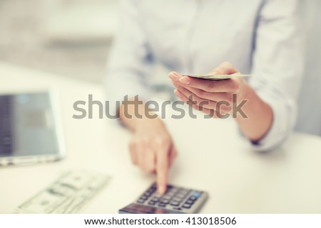 savings, finances, economy, technology and people concept - close up of woman counting money with calculator - stock photo