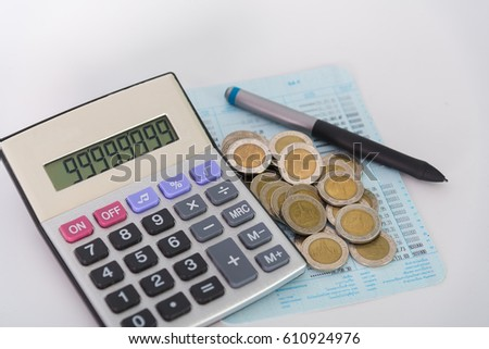 Savings, increasing columns of coins, piles of coins arranged as a graph and calculator with pen on white background, business idea, shallow focus.