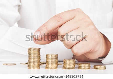 Savings, male hand stacking gold coins into increasing columns - stock photo