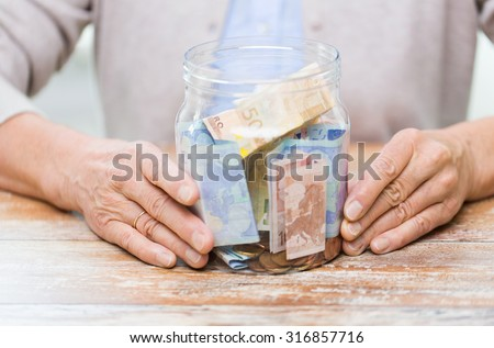 savings, money, annuity insurance, retirement and people concept - close up of senior woman hands with money in glass jar - stock photo