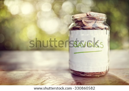 Savings money jar full of coins concept for saving or investment for a house, retirement or education - stock photo