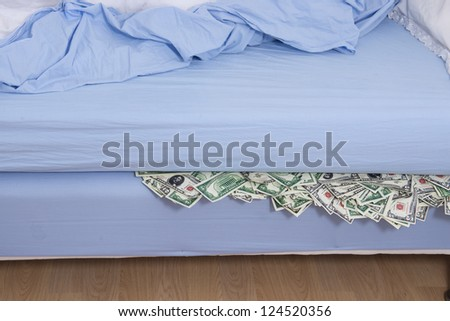 Savings or bank run concept: Hiding US dollars under the mattress - stock photo