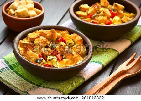 Savory baked vegetarian bread pudding made of zucchini, bell pepper, tomato and diced baguette, photographed with natural light (Selective Focus, Focus on the zucchini pieces in the front)