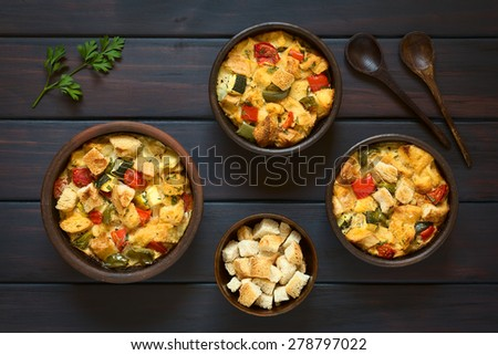 Savory baked vegetarian bread pudding made of zucchini, bell pepper, tomato, diced baguette with thyme and parsley in rustic bowls, photographed overhead on dark wood with natural light - stock photo