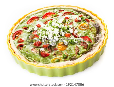 Savory egg, herb, tomato and cheese vegetarian quiche in a pastry crust served in a fluted pie dish on a white background
