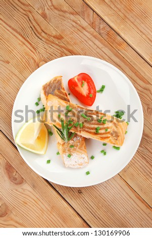 savory fish portion : roasted norwegian salmon chunks on white dish over wooden table