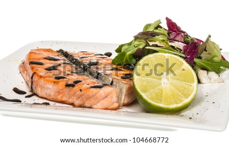 savory fish portion : roasted norwegian salmon fillet garnished with salad and basil leaves and lime on white dish isolated with balsamic sause - stock photo