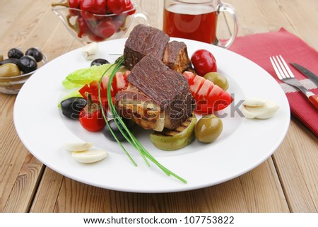 savory food : roast beef garnished with apple juice , green and black olives, red hot peppers on wooden table - stock photo