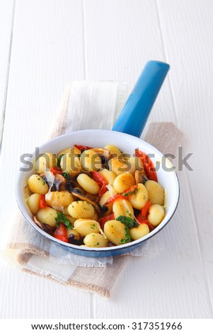 Savory Italian gnocchi with autumn mushrooms, herbs and tomato, served at a restaurant in a blue frying pan, high angle view - stock photo
