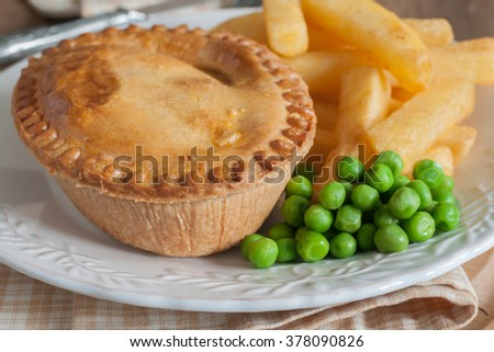 Savory meat pie with chips or fries and green peas  - stock photo