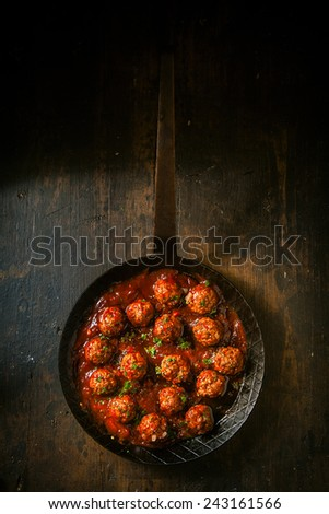 Savory meatballs in a piquant spicy sauce garnished with fresh herbs, overhead view in a frying pan or skillet on a rustic wooden table - stock photo