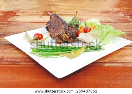 savory plate over wooden table: grilled ribs on white plate with chives, red hot peppers lettuce - stock photo