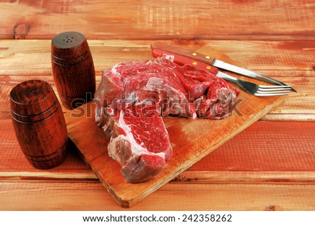 savory: red raw beef meat steak on wooden cutting board prepared for roasting - stock photo