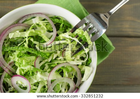 Savoy cabbage and onion salad served in bowl on wooden table