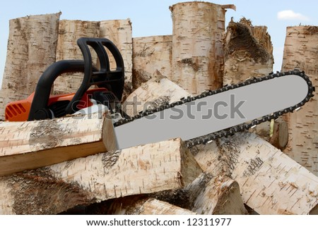 saw on a background of wooden logs - stock photo