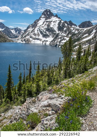 Sawtooth Lake in Idaho wilderness framed with pine trees and rugged snow capped mountain peaks. - stock photo
