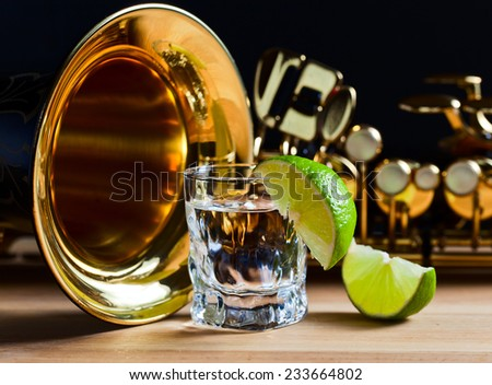 saxophone and tequila with lime on wooden table - stock photo