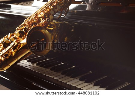 Saxophone lying on the piano, close up - stock photo