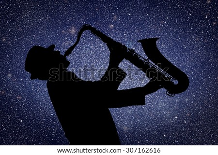 Saxophonist. Man playing on saxophone against the background of starry sky - stock photo