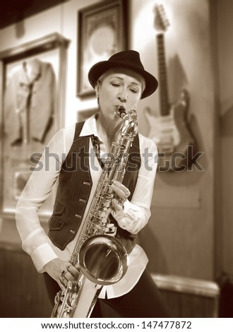 Saxophonist. Middle aged woman playing on saxophone against the background of rock cafe - stock photo