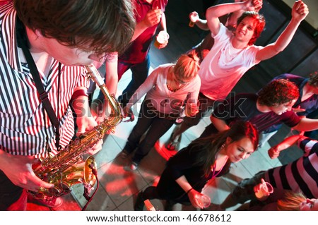 Saxophonist playing in a nightclub, with dancing people in the background - stock photo