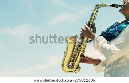 Saxophonist playing on saxophone on blue sky background  - stock photo